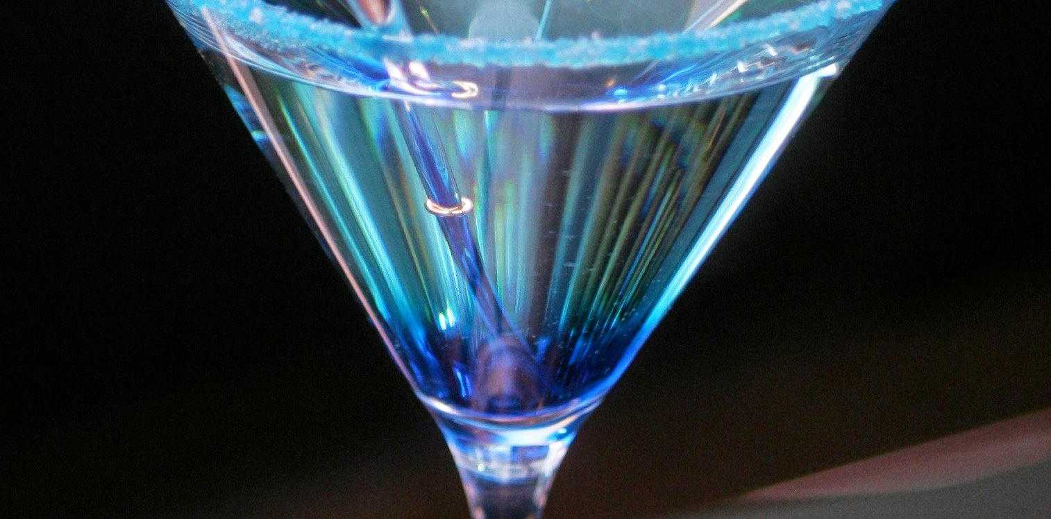 A sapphire martini made from Blue Curacao, Sapphire Bombay gin and a dash of dry vermouth served in a glass rimed with blue sugar.