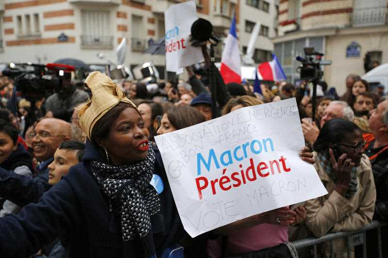 Supporters of French independent centrist presidential candidate, Emmanuel Macron react outside his campaign headquarters in Paris, France, Sunday, May 7, 2017. Polling agencies have projected that centrist Emmanuel Macron will be France's next president