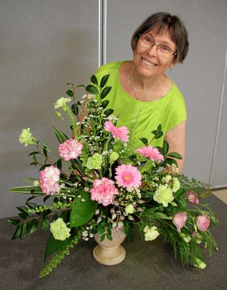 IN BLOOM: Floral Art Society of Qld member Eleanor Lydon with her beautiful floral design.