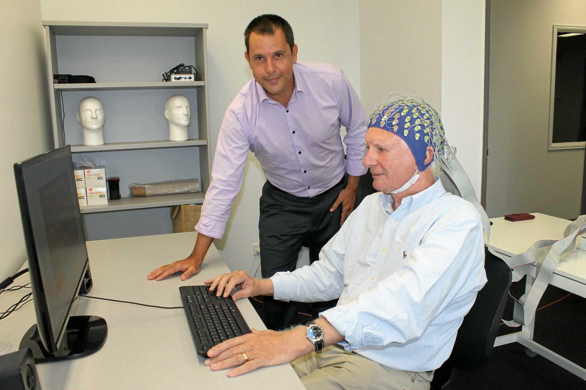 USC PhD student Ben Isbel showing a volunteer the neuroscience equipment at the Sunshine Coast Mind & Neuroscience - Thompson Institute.