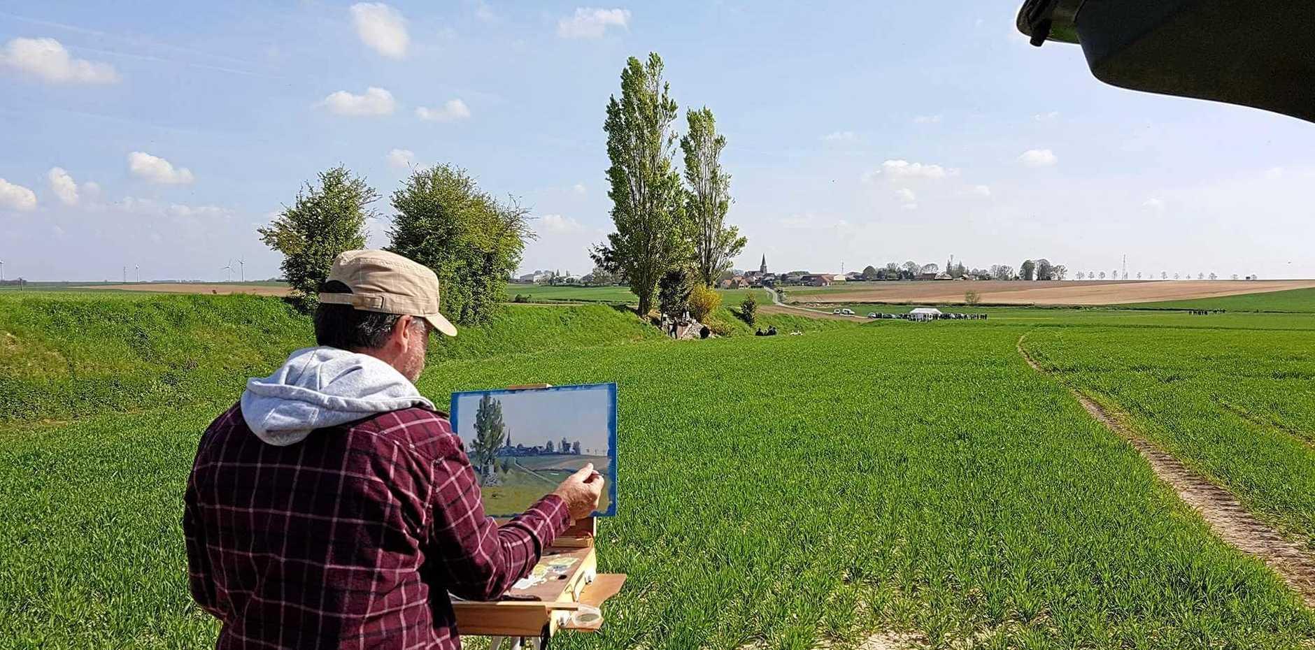 Sunshine Coast artist Garry Dolan paints a scene of the battlefield near the petite cross in Bullecourt.