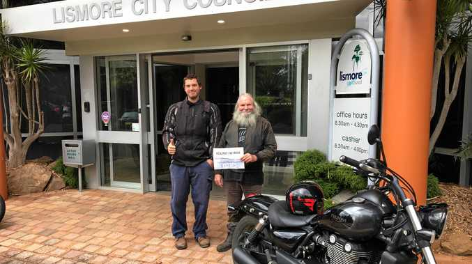 Kyogle's Peter 'Kog' Godfrey and his son, James making a generous donation of money raised from the showing of their film to the Lismore Council Flood Appeal.