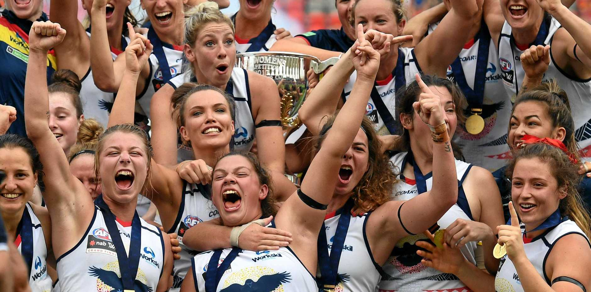 Adelaide Crows players celebrate winning the AFLW grand final against the Brisbane Lions.
