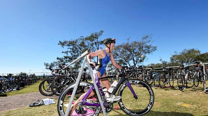 Alexandra Barnes grabs her bike during the Byron Bay Triathlon at Main Beach in Byron Bay.