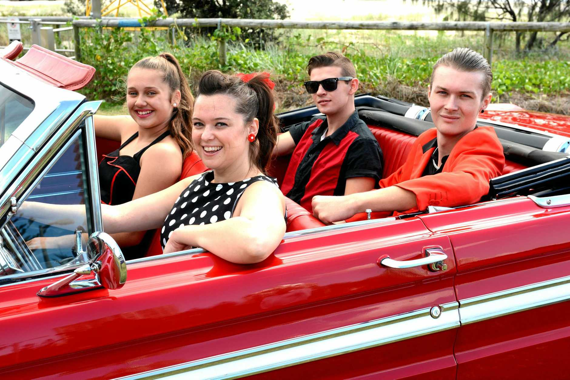 Cadillac Rock 'n' roll dancers Emma Wilkinson, Natalie Rowe, Jake Maloney and Mitch Vaegdom check out a vintage Ford at Coolangatta on Thursday