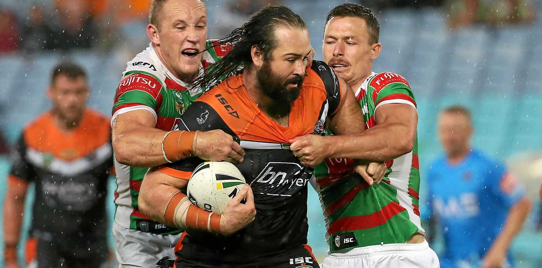 Aaron Woods of the Tigers (centre) powers his way through the Rabbitohs defence.