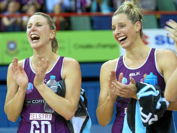 Former players Clare McMeniman (left) and Laura Geitz celebrate a Firebirds win.