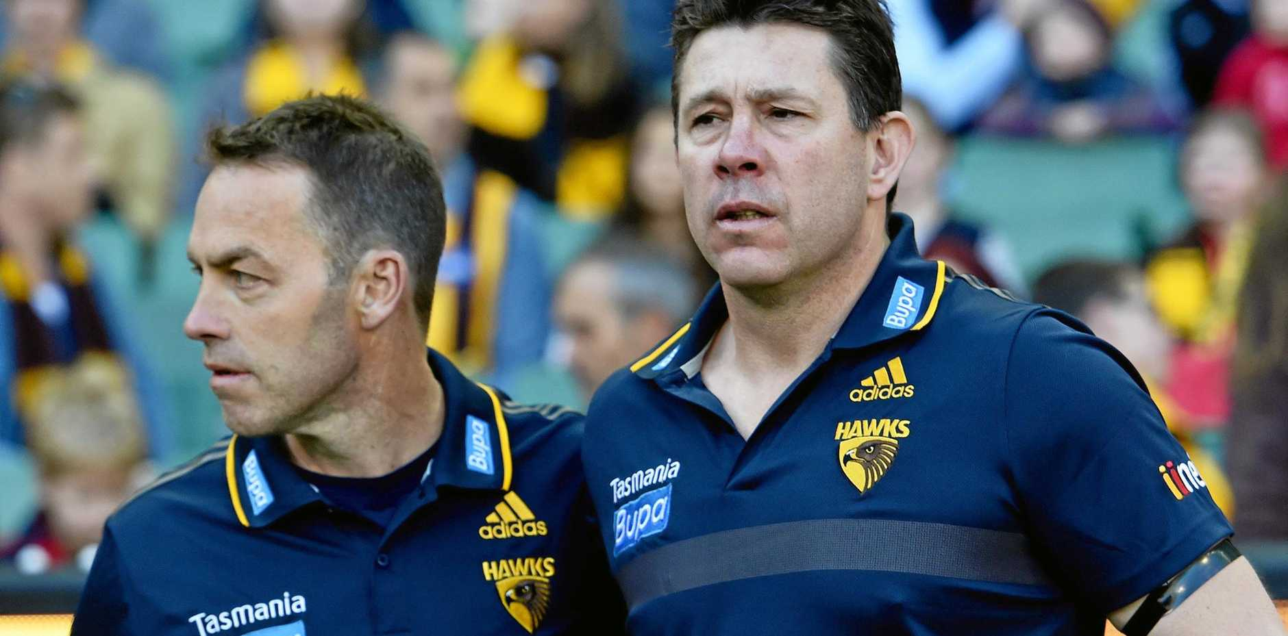 Hawks coach Alastair Clarkson (left) and assistant Brett Ratten watch as players run through a tribute banner for Cooper Ratten in September 2015.
