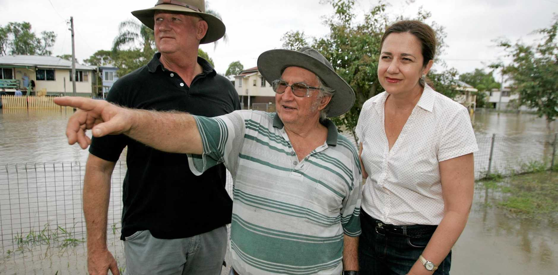 A war of words has erupted between the State and Federal Governments over flood funding. Pictured in 2013 is Depot Hill resident Wayne Wisley (centre) points to where the flood waters came up to in 2010 as L-R local member Bill Byrne and opposition leader Annastacia Palaszczuk look on as the Fitzroy River rises past 8.2 to an estimated 8.5 peak at Rockhampton.