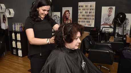 Hairdresser Kerry Prendergast cuts Donna Flint-McKenzie's hair at her Margaret Street salon
