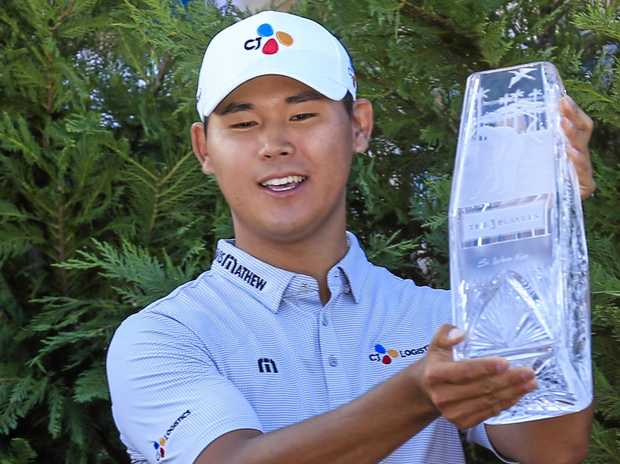 Si Woo Kim of South Korea smiles as he holds up the winner's trophy after taking out the Players Championship.