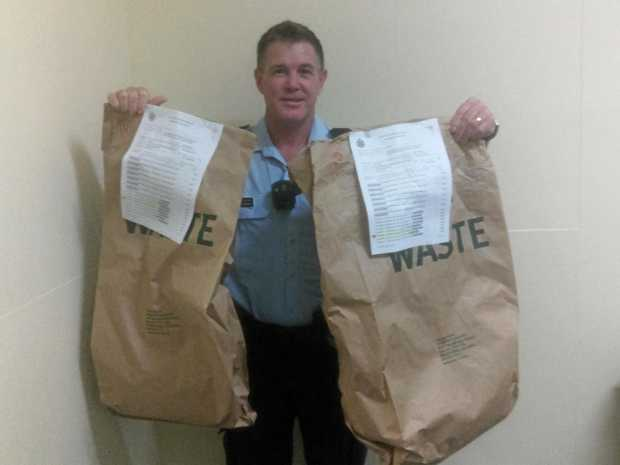 HAUL: Senior Constable Pat Bennett holds two bags containing more than 1.5kg of cannabis seized during Operation Papa Advance.