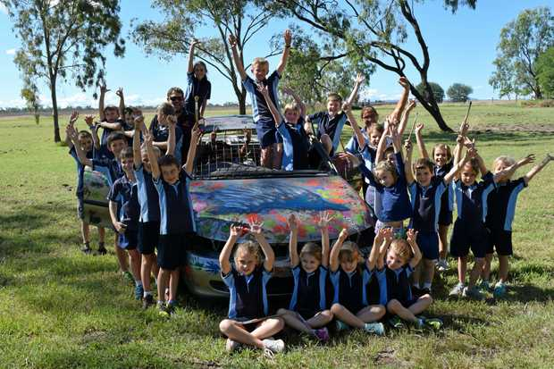 Jambin State School students with chappy Nigel Krueger and the car they painted up for the Crash-A-Rama at the show tomorrow.