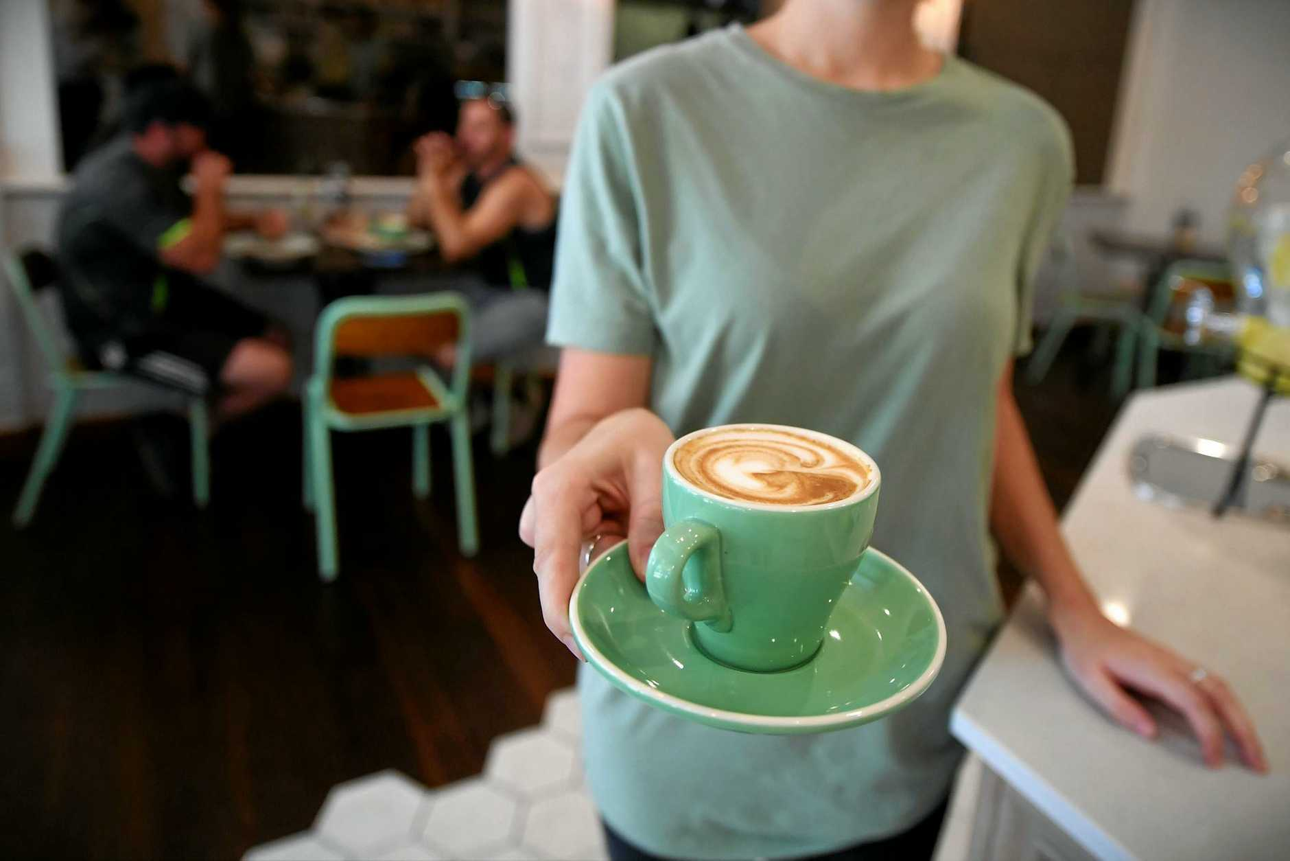 A waitress is seen holding a coffee at a cafe in Canberra. The Fair Work Commission yesterday announced cuts to Sunday and public holiday penalty rated in the retail and hospitality industries.