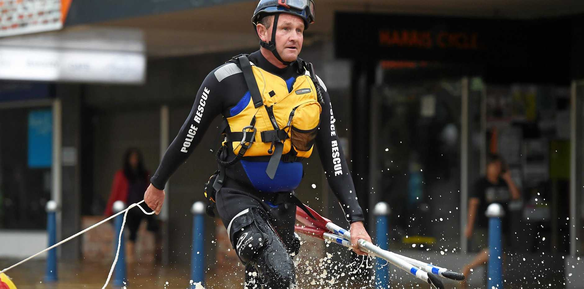 Senior Constable Peter 'Nudge' Ellis rushes to the aid of Deon Ord who was trapped by rising flood waters on Keen Street.