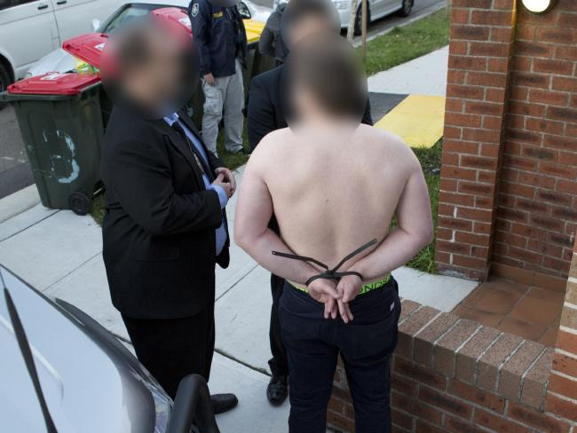 Adam Cranston, son of ATO boss Michael Cranston, is arrested at his Bondi flat yesterday over his role a $165 million fraud syndicate. Picture: Police Media