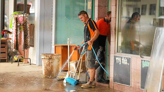South Murwillumbah Prospero Street Butchers resembles a war zone as Alfred Smith hoses mud and slush out due to heavy flooding after Thursday nights rain deluge caused the Tweed River to break its banks.Photo: Scott Powick Daily News
