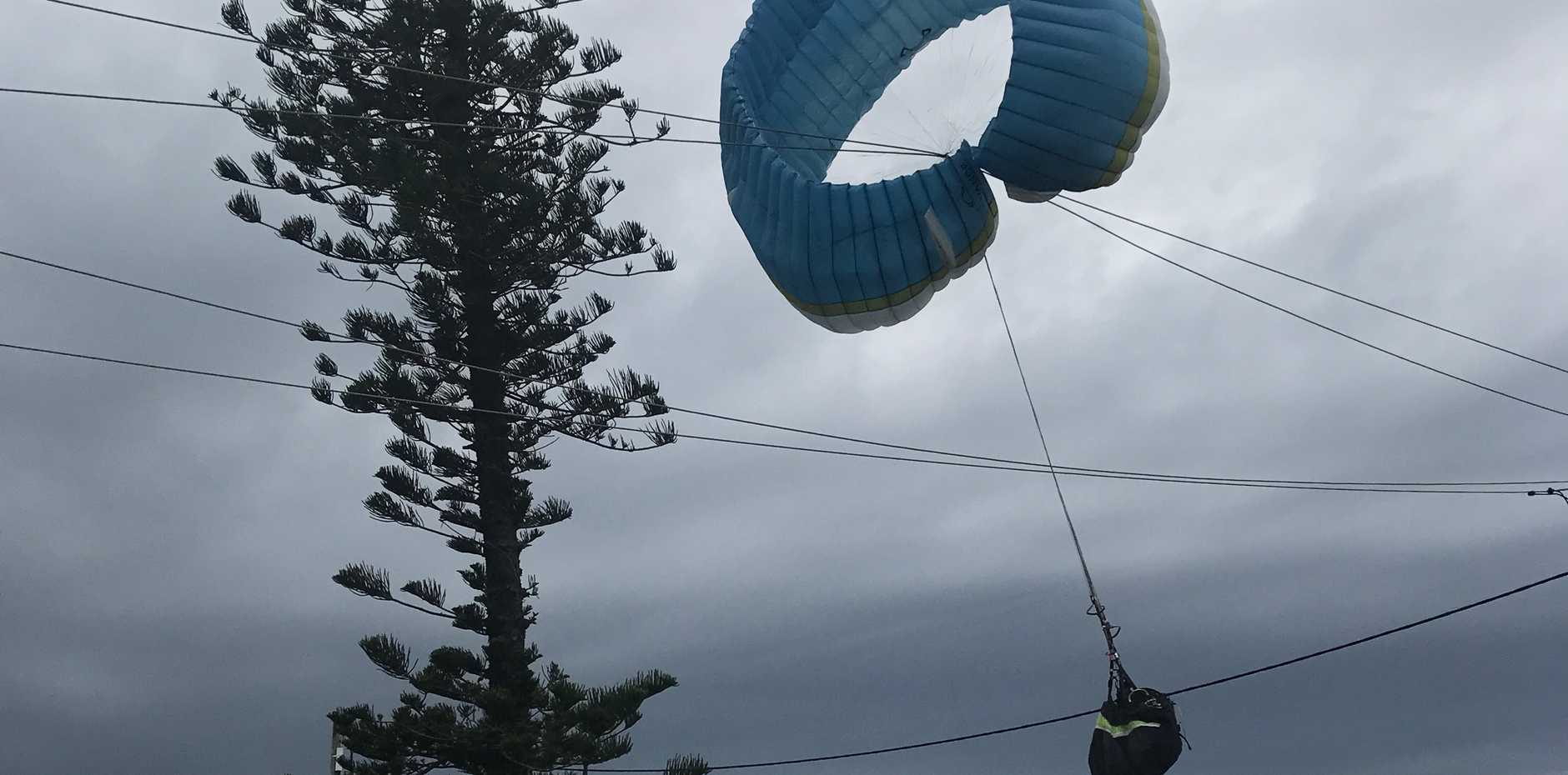 A paraglider has escaped injury after his kite became tangled at Sunshine Beach.