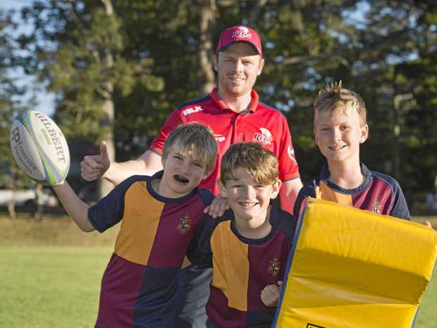 Downs Rugby development officer Dan Birrell with TACAPS under 12 players (from left) Robbie Wilson, Robert Russell and Joseph Anderson.