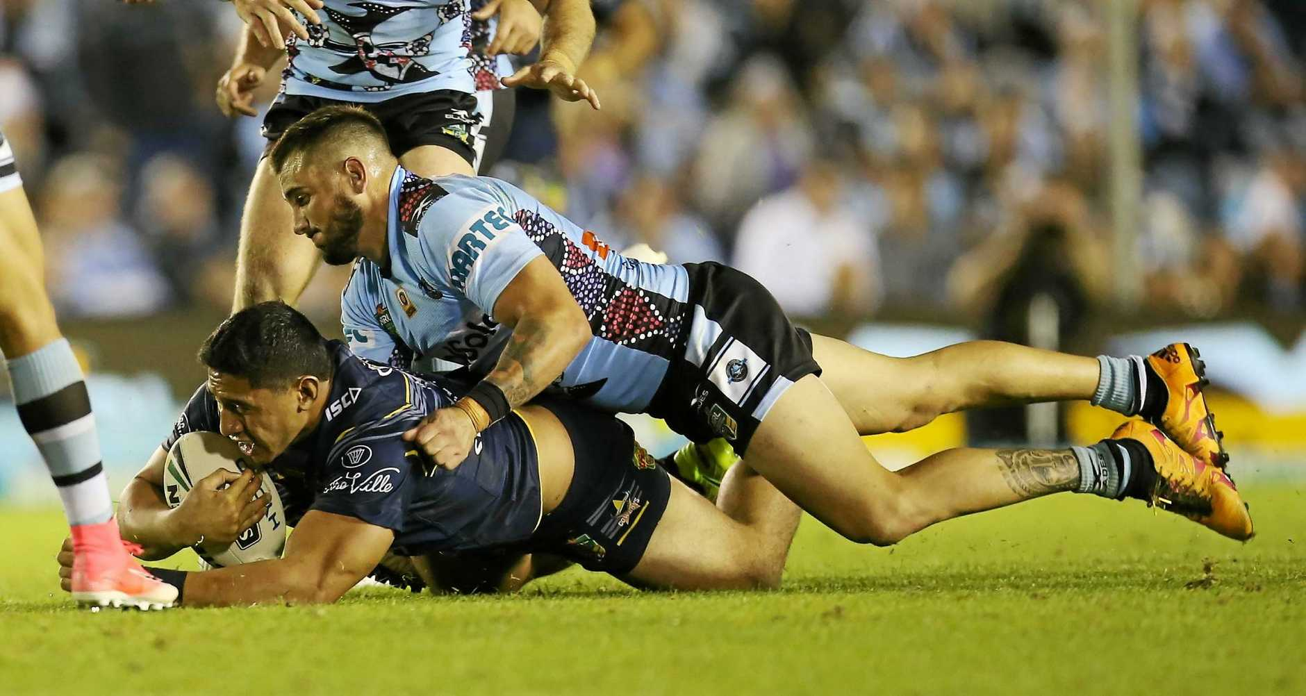 Jack Bird and Chad Townsend of the Sharks tackle Jason Taumalolo of the Cowboys.