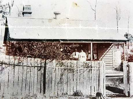 A man and a woman stand on the front verandah of Gatehouse Cottage in 1913.
