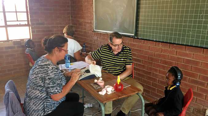 REACHING OUT: Audiologist Greg Butcher tests the hearing of a child in South Africa.