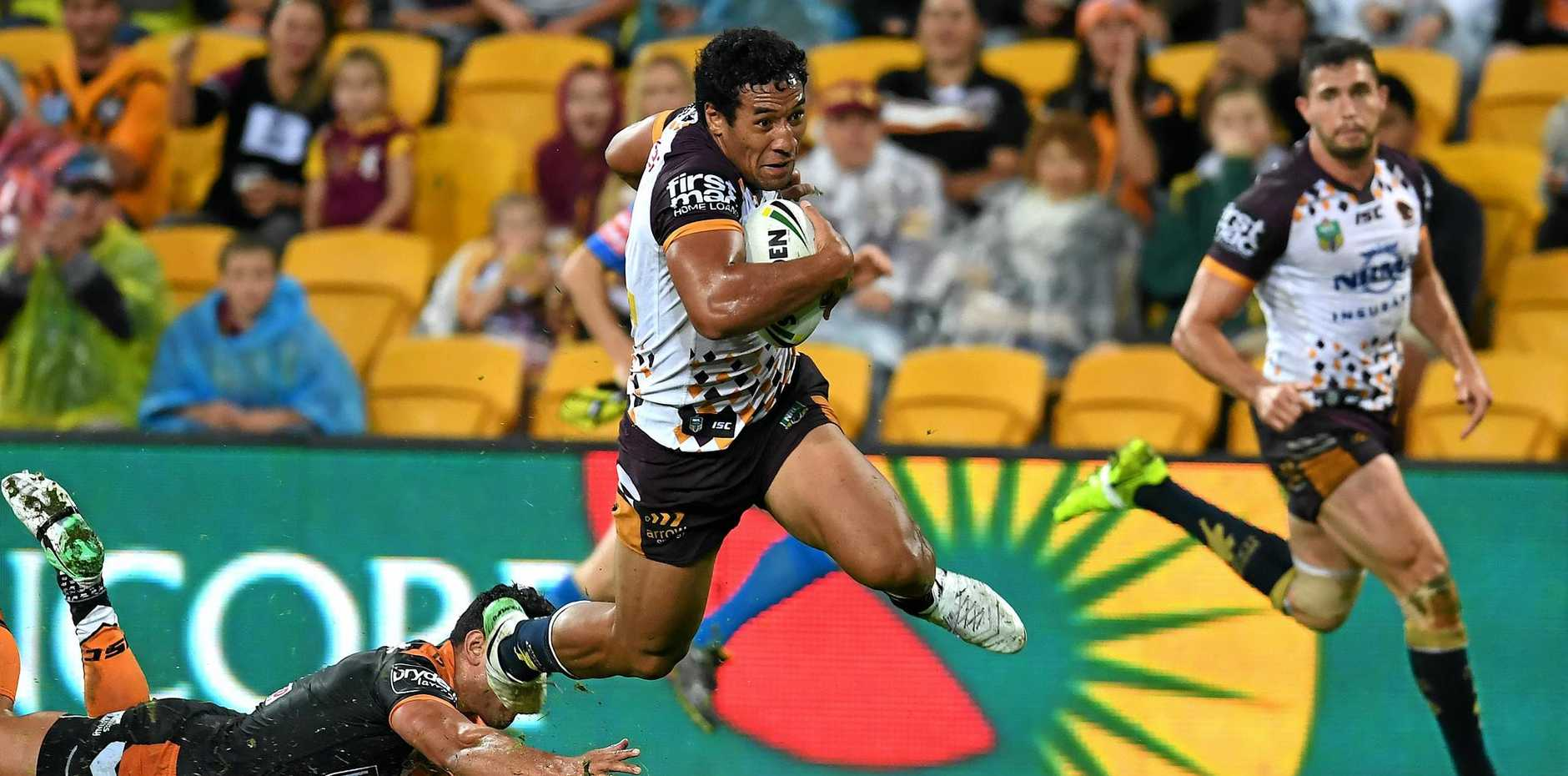 Tautau Moga of the Brisbane Broncos leaps over the Wests Tigers defence to score a try.