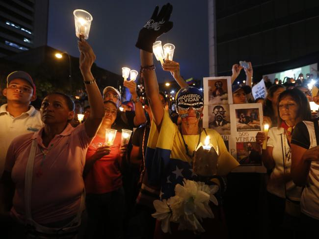 Demonstrators hold candles during a vigil for the victims of the clashes with the Venezuelan government security forces.