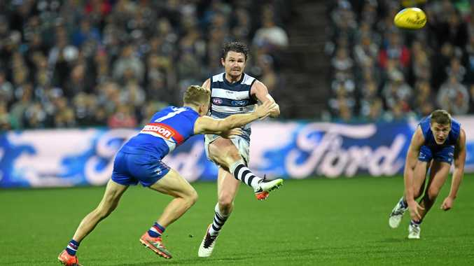 Patrick Dangerfield of the Cats gets a kick away under pressure.