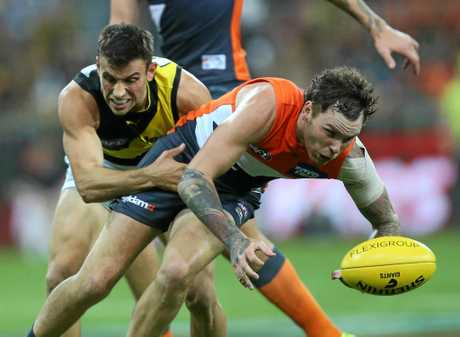 Trent Cotchin of the Tigers (left) tackles Harry Perryman of the Giants.