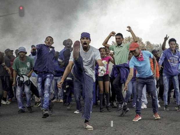 Protesters sing and chant in front of a burning barricade in the Ennerdale, Johannesburg township, Tuesday May 9, 2017. Violent protests have erupted in South Africa's biggest city for a second day, with police firing rubber bullets at demonstrators who blocked roads and burned tires.