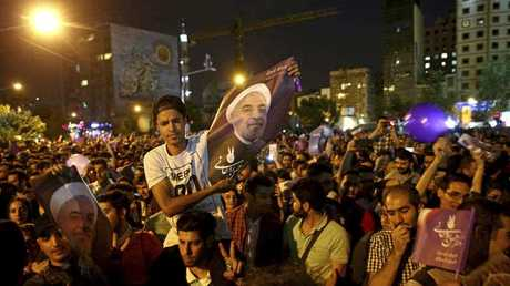 Supporters of Iranian President Hassan Rouhani celebrate after he won the presidential election in Tehran, Iran, Saturday, May 20, 2017. Tens of thousands of supporters of President Hassan Rouhani have poured into the streets of Tehran as night falls to celebrate the incumbent's re-election.