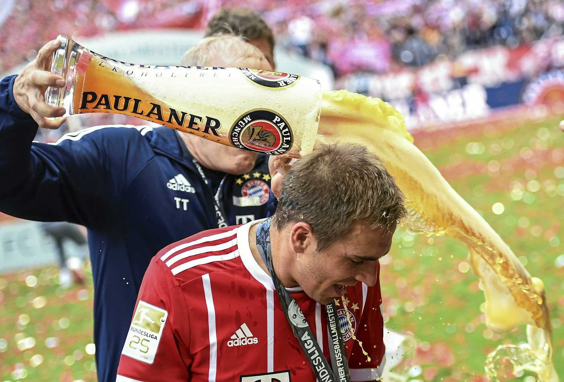 Bayern Munich's Philipp Lahm receives a beer shower from assistant coach Hermann Gerland.