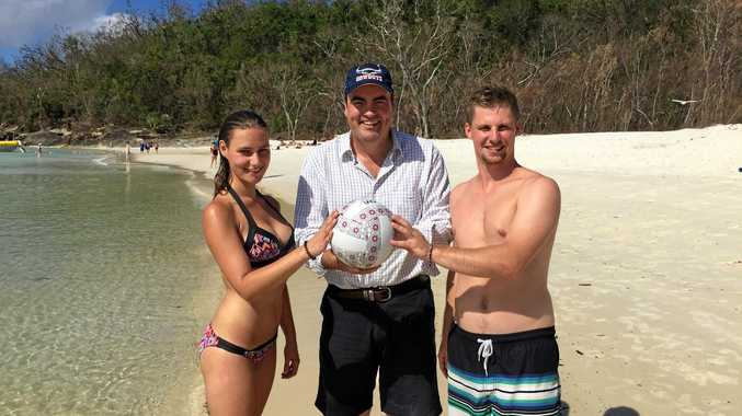 German backpackers Anne Maehlitz and Sebastian Grundmann with Whitsunday MP Jason Costigan on iconic Whitehaven Beach, a perfect spot to host beach volleyball in the Commonwealth Games.