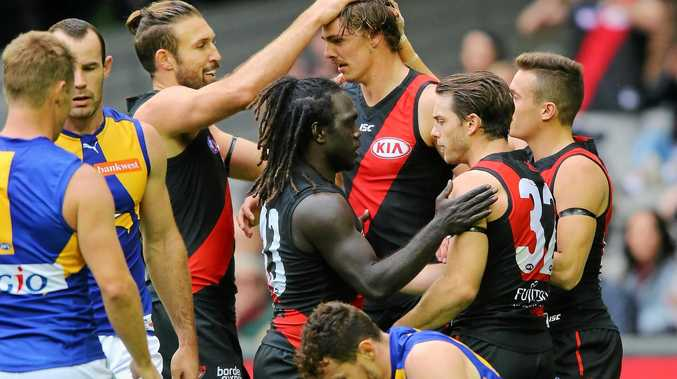 Joe Daniher is congratulated by Essendon teammates after kicking one of his five goals.