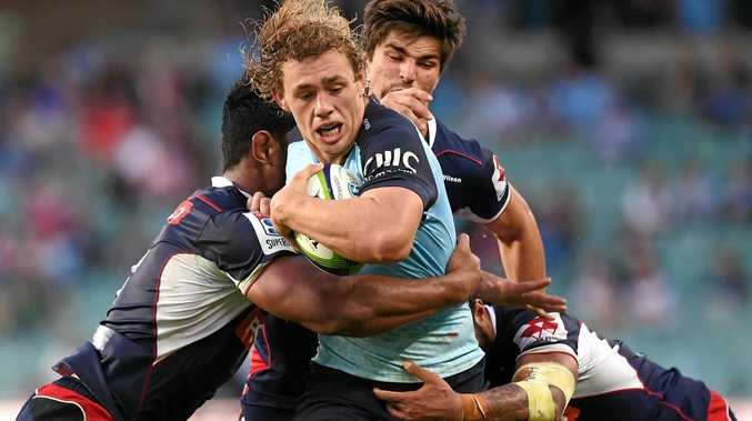 Ned Hanigan (centre) of the Waratahs is tackled by Lopeti Timani (left) and Amanaki Mafi of the Rebels.