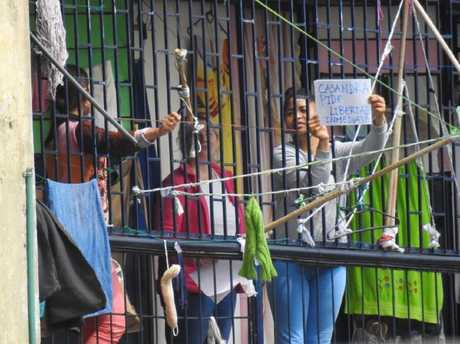 """Cassie Sainsbury (centre) beside an inmate holding a sign written in Spanish, which translated means """"Cassandra asks freedom immediately""""."""