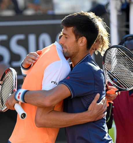 Zverev is congratulated by  Novak Djokovic