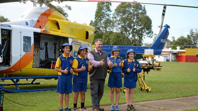 The RACQ Capricorn Rescue Helicopter landing at Mount Archer school to launch the 'Streets Ahead' program. School captains Caylis Lewis, Tyrelle Pope, Storm Duke and Ellie Bloomfield with Cr Neil Fisher.