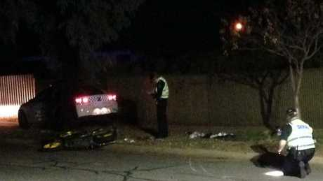 Detectives examine the scene where a police car crashed into a motorcycle.