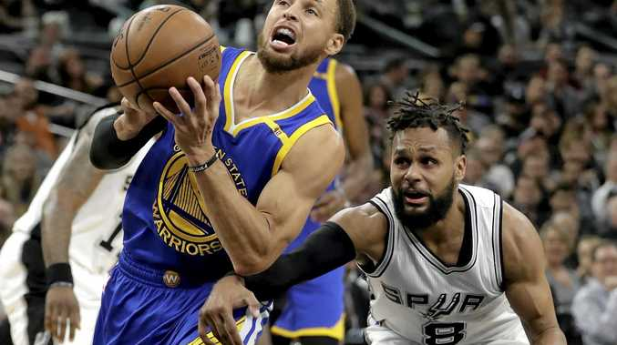 Golden State's Stephen Curry (left) drives past San Antonio's Patty Mills.
