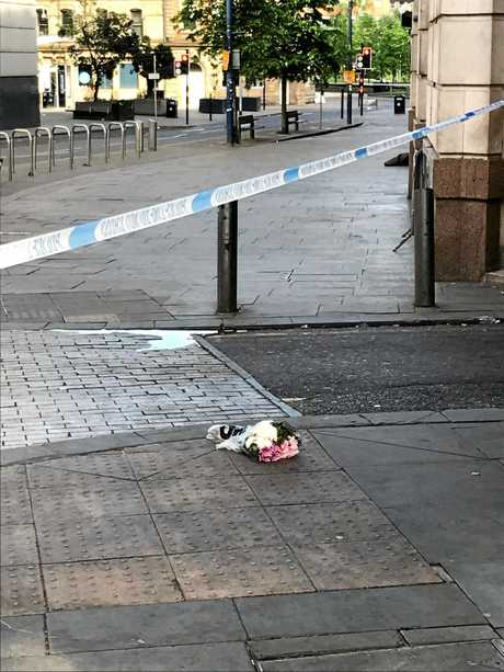 SCENE: Flowers laid on the floor where the area has been cordoned off.