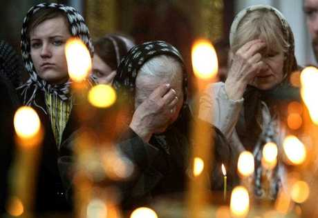 Women cross themselves during a public prayer for the victims of terrorist bomb attack in an orthodox church in Minsk, Belarus 12 April 2011.