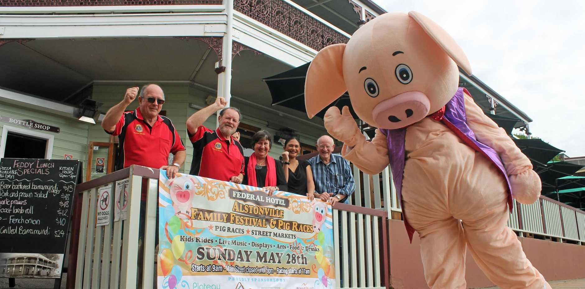 RUN, PIGGY, RUN: Members of the Alstonville Lions Club and the Alstonville-Wollongbar Chamber of Commerce join Federal Hotel staff in cheering on the pig promoting the Alstonville Family Festival.