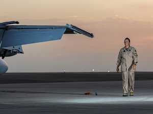 Royal Australian Air Force Operations and Airside Safety Officer Squadron Leader Alesha Cantelo, from the Air Task Group, walks past an F/A-18A Hornet aircraft during her deployment at the main air operating base in the Middle East Region.