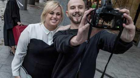 A fan stops Wilson for a selfie outside court.
