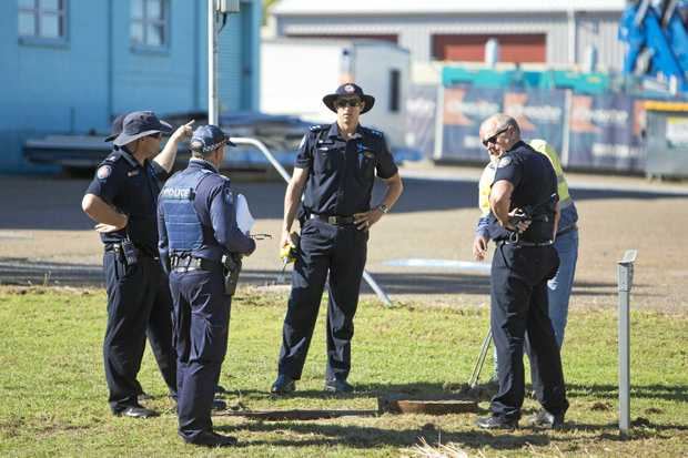 WHAT TO DO NEXT: Police discuss the situation next a manhole at the scene where a body has been found in a stormwater drain.