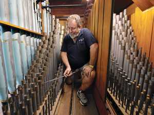 Organ builder Simon Pierce tunes the flute pipes on St Paul's Uniting Church organ.