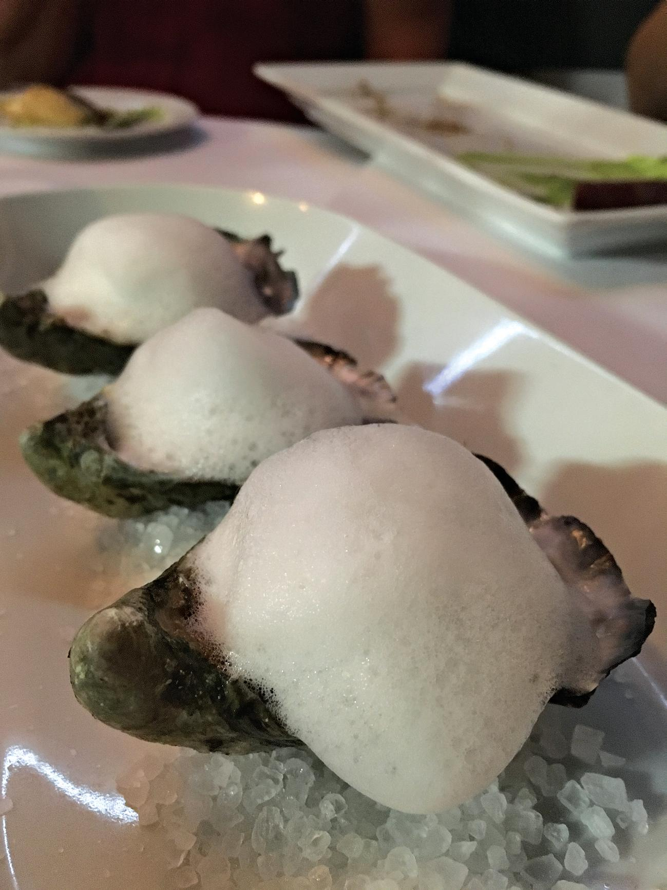 Oysters with finger lime and coconut water foam.