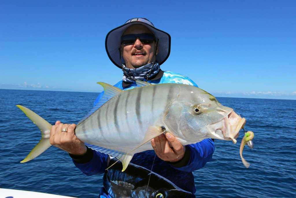 Scott with a golden trevally caught with Hervey Bay Fly and Sportfishing.